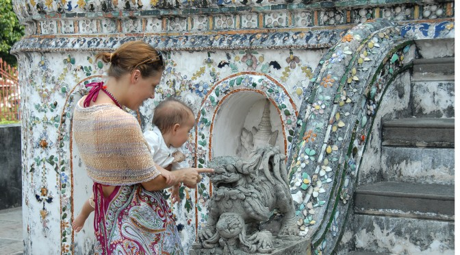 mom and baby inspect dragon statue